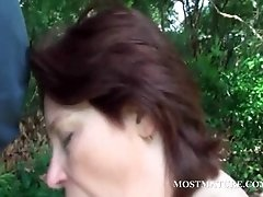 Naked mommy blows hard pecker outdoor
